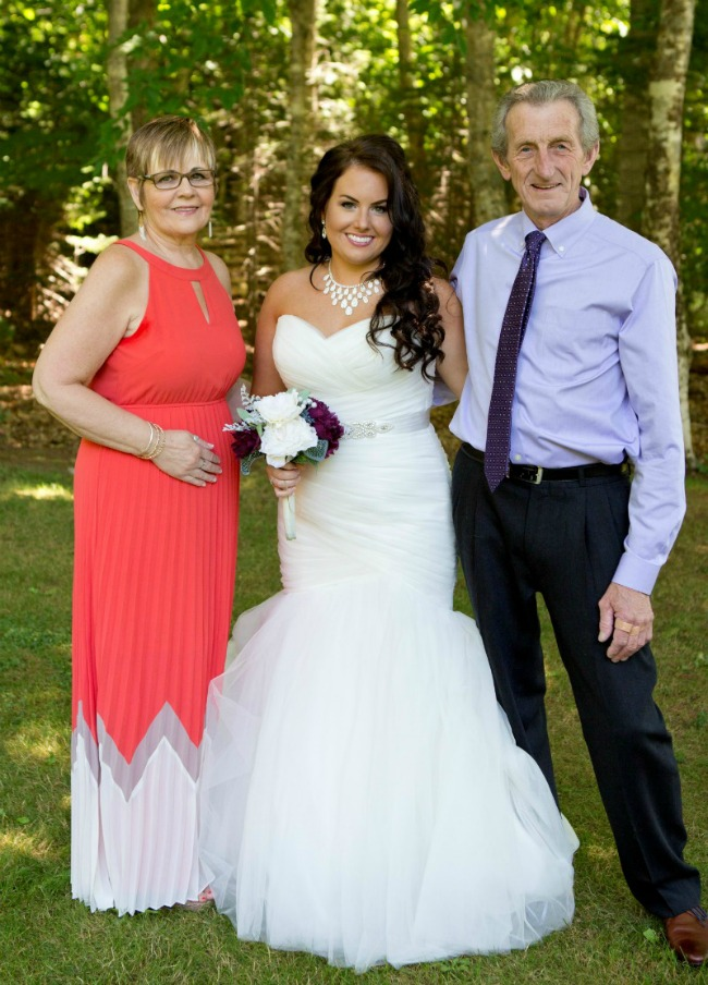 mother of the bride in orange and white colorblock gown standing beside bride and father of the bride