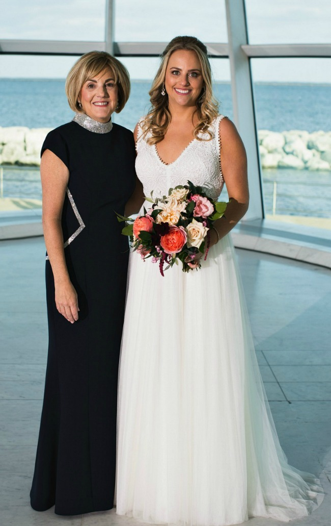 mother of the bride Audrey wearing navy gown standing beside bride