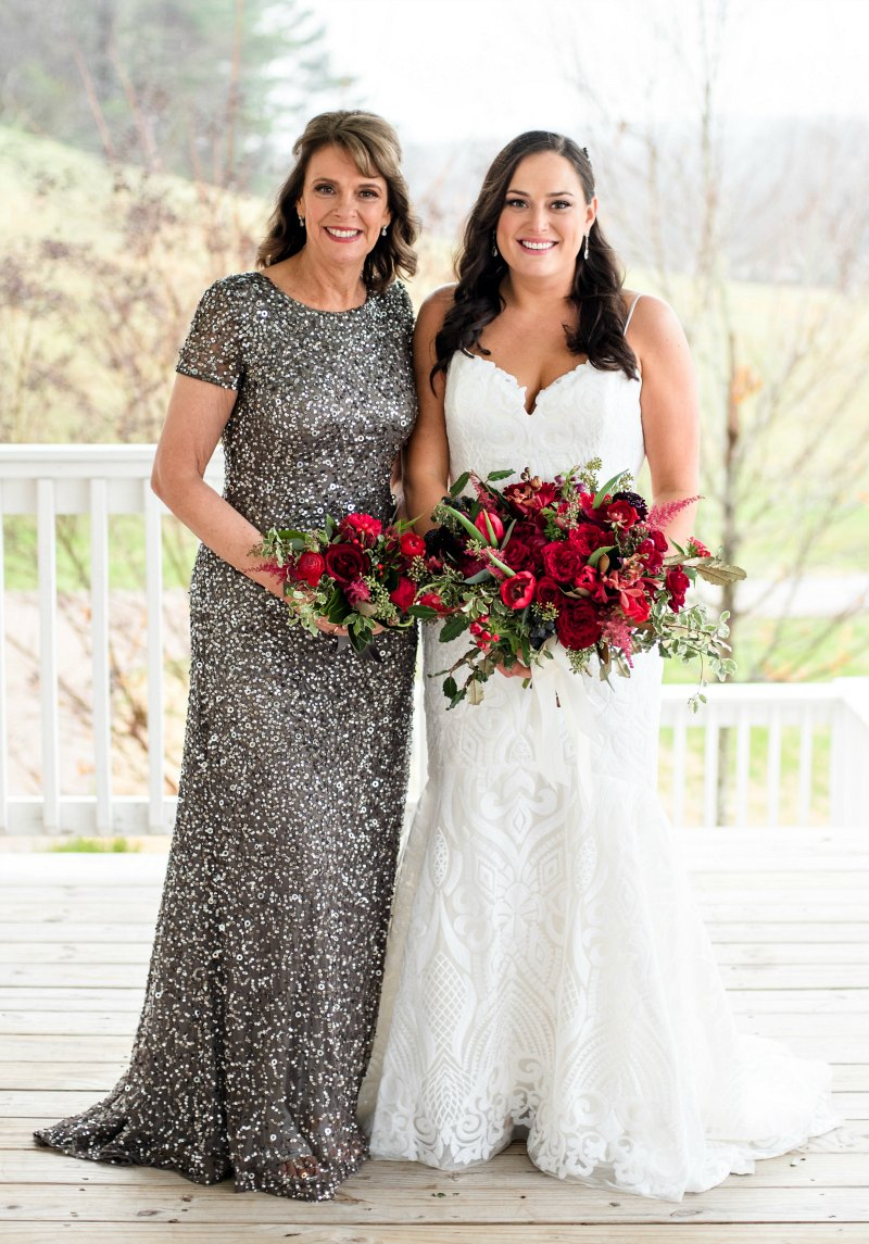Mother of the bride dress in long, gray sequinned gown holding red flowers, standing beside bride at December wedding