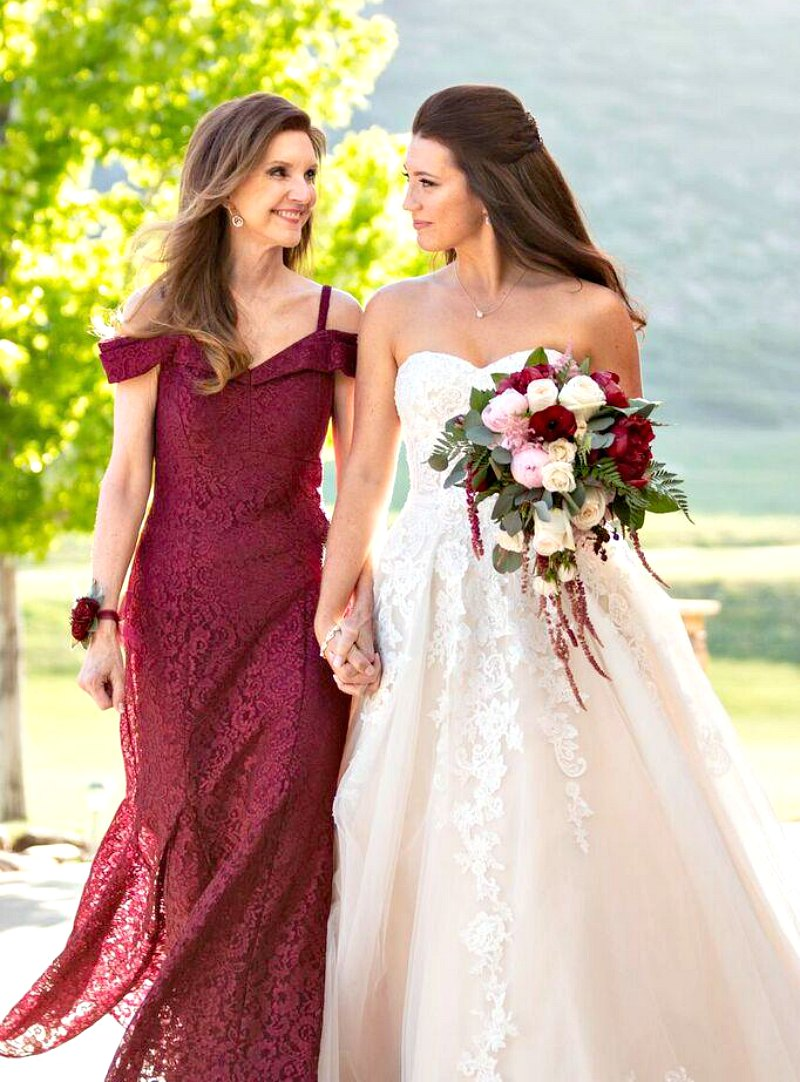 Mother of the bride dress - wearing wine colored off the shoulder lace gown walking with bride